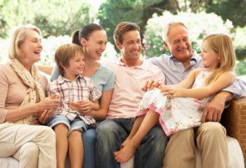 Three Generation Family Sitting On Sofa Together